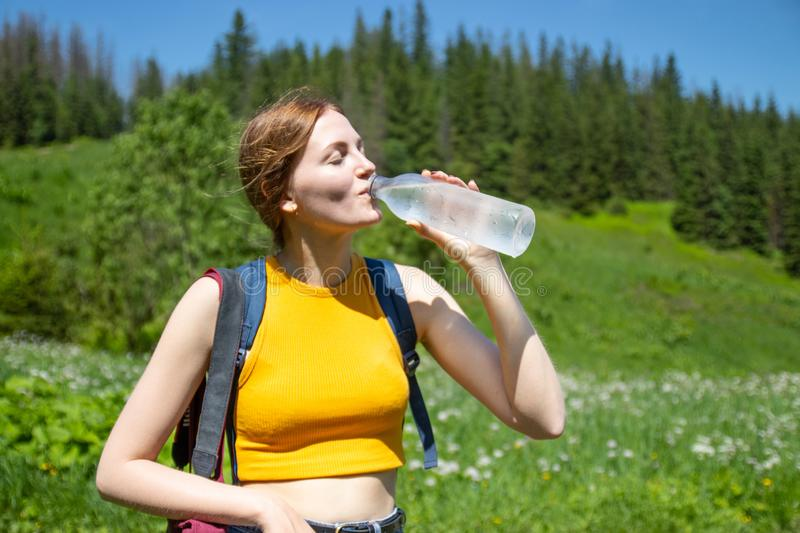 Female tourist drink water from a plastic bottle.Woman resting in the mountains. royalty free stock photos