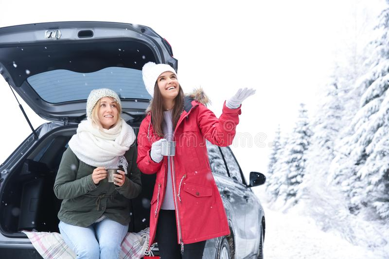 Female tourist drinking tea near car. In snowy countryside stock photos
