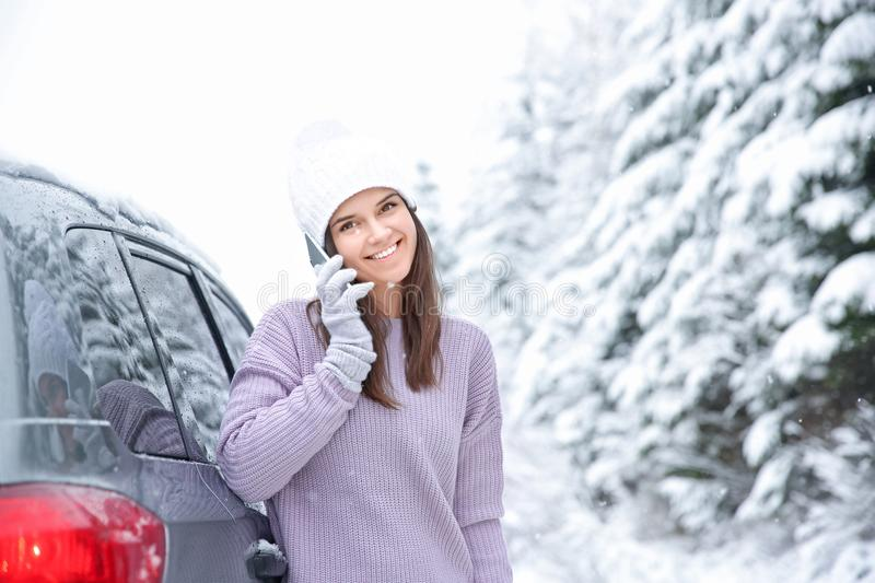 Female tourist drinking tea near car. In snowy countryside stock photography