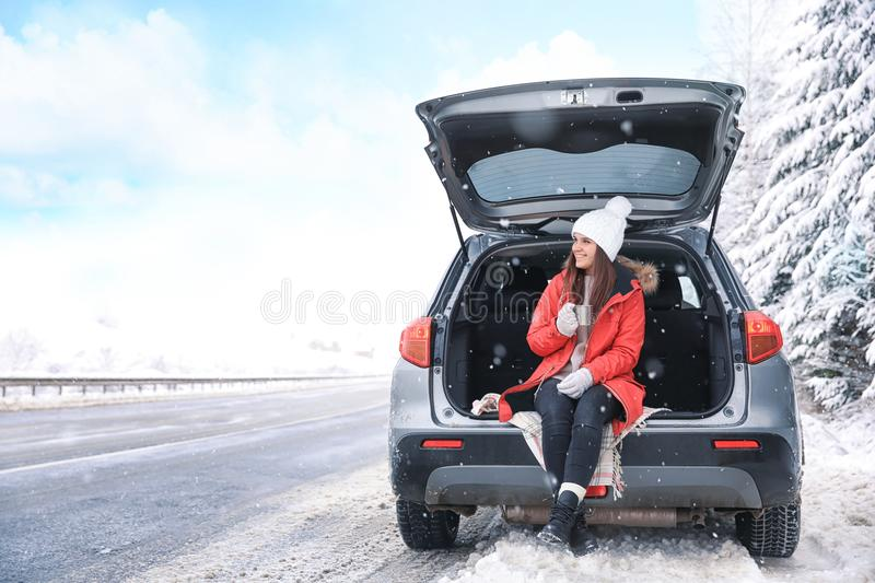 Female tourist drinking tea near car. In snowy countryside stock photo