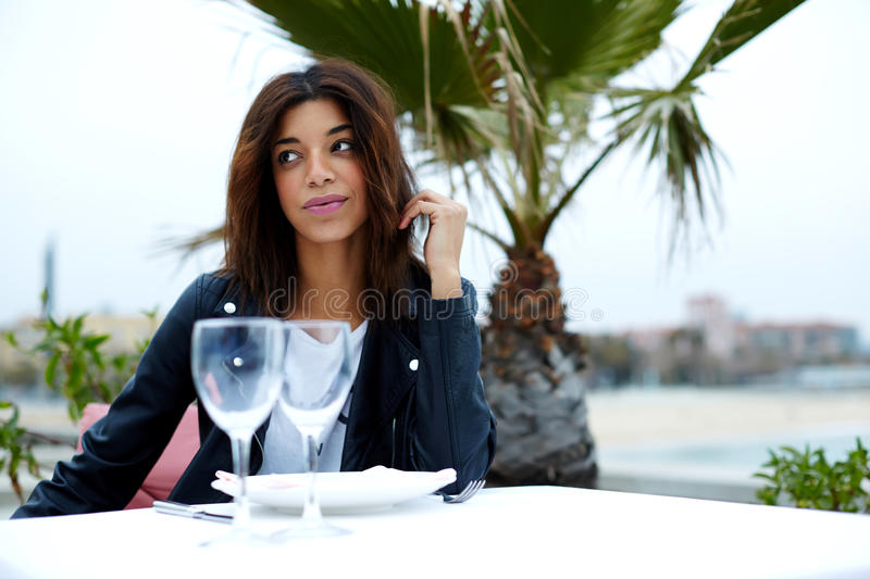 Female tourist enjoying her recreation time in restaurant on seashore with palm tree on background royalty free stock image