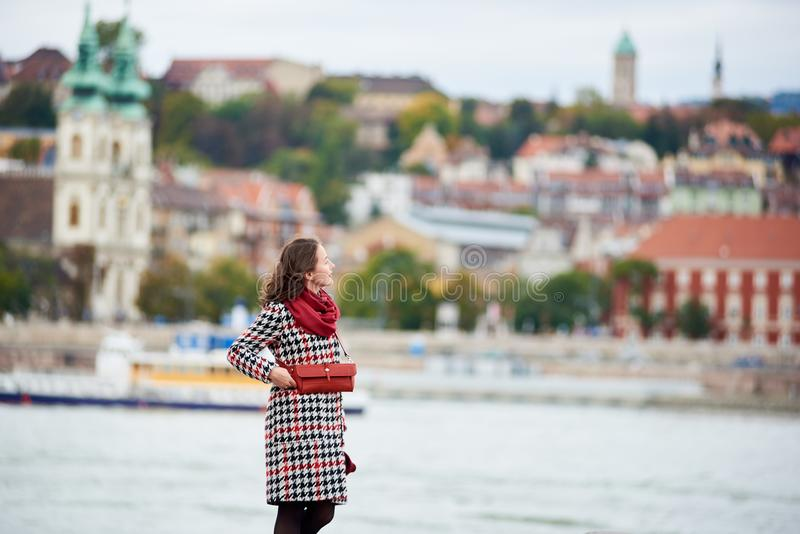 Female tourist is enjoying view of Buda side of Budapest. With the Buda Castle, St. Matthias and Fisherman`s Bastion. Background blurred. Her hair is blown by royalty free stock photos