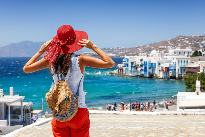 Female tourist enjoys the view to the town of Mykonos island, Greece. Female tourist with red hat enjoys the view to the town of Mykonos island, Little Venice stock images