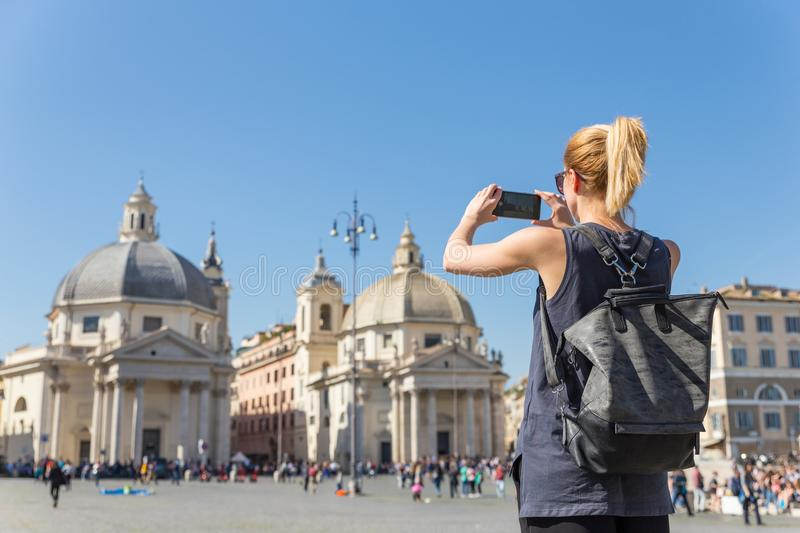Female tourist with a fashinable vintage hipster backpack taking photo of Piazza del Popolo in Rome, Italy by her mobile. Female tourist with a fashinable royalty free stock images