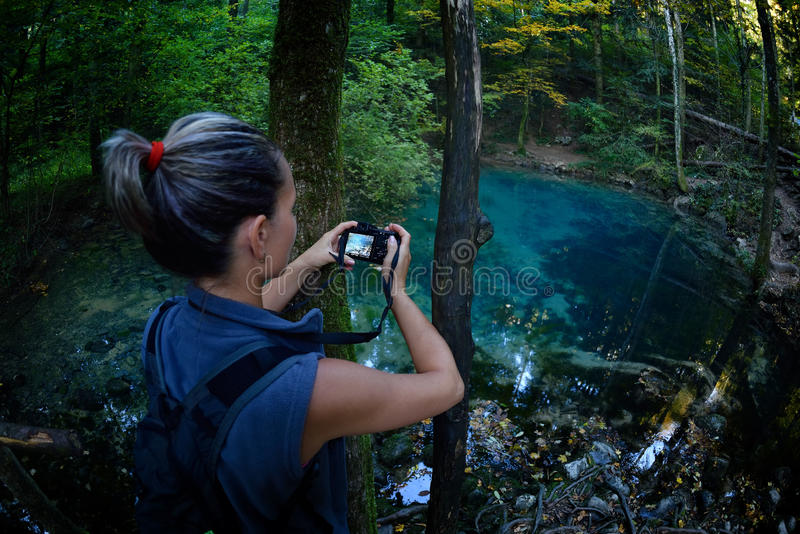 Female tourist in the forest. Taking photos royalty free stock photography