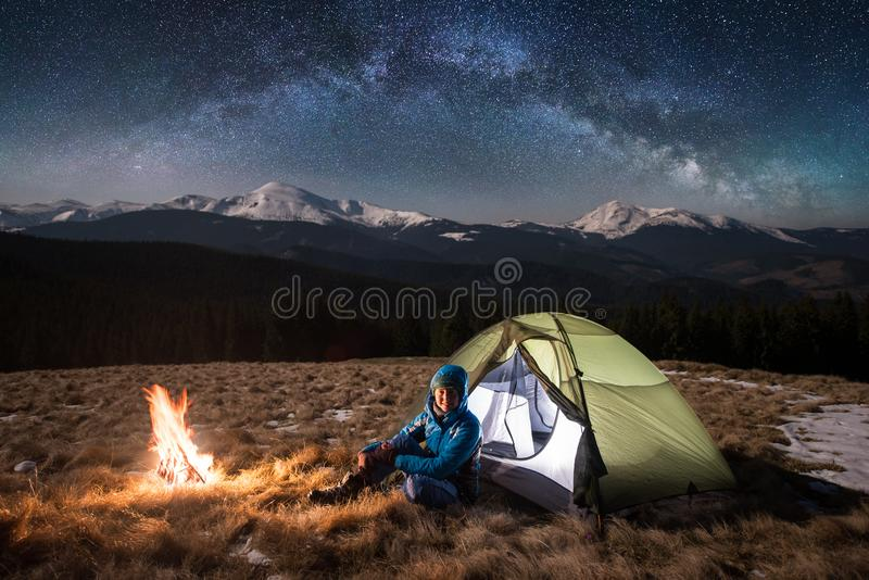 Female tourist in her camp at night. Happy woman under beautiful sky full of stars and milky way. Female tourist in her camp at night. Happy woman looking to the stock image