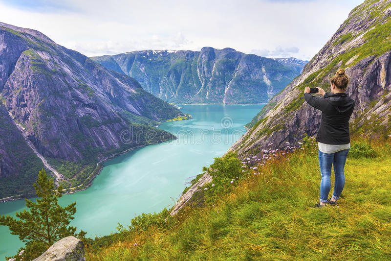 Female tourist hiking in high norwegian mountains over a fjord. Woman hiking tourist in the high norwegian mountains over a beautiful fjord royalty free stock photos