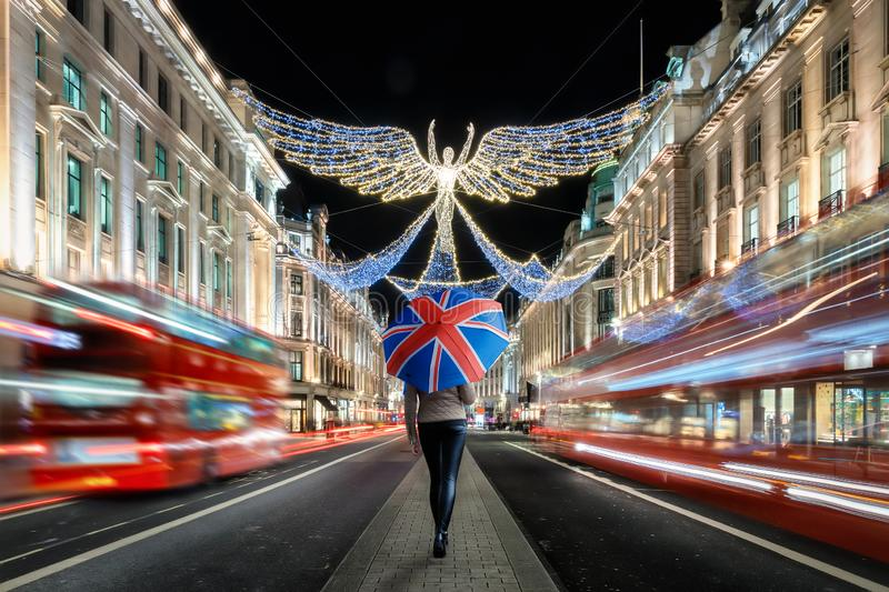 A female tourist holding an umbrella with a british flag on it explores the christmas decorated city center of London, United King. Dom, during ight time with stock images