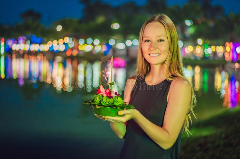 A female tourist holds the Loy Krathong in her hands and is about to launch it into the water. Loy Krathong festival. People buy flowers and candle to light royalty free stock photos