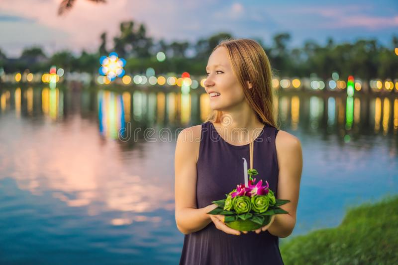A female tourist holds the Loy Krathong in her hands and is about to launch it into the water. Loy Krathong festival. People buy flowers and candle to light stock photos