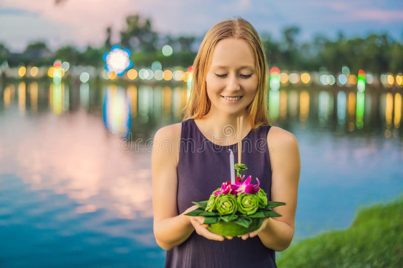 A female tourist holds the Loy Krathong in her hands and is about to launch it into the water. Loy Krathong festival. People buy flowers and candle to light stock photography