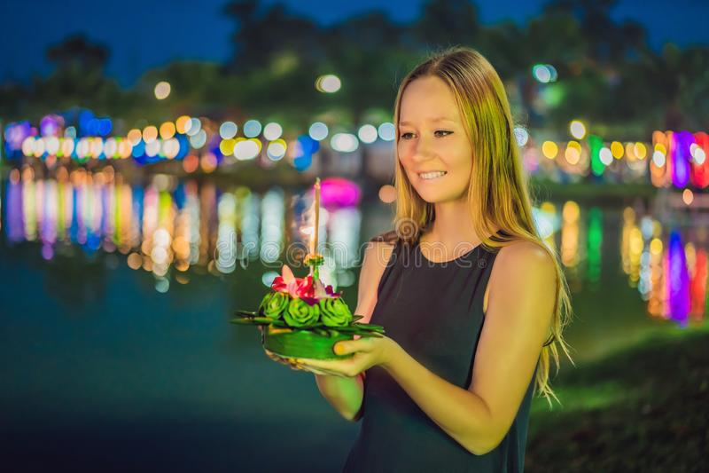 A female tourist holds the Loy Krathong in her hands and is about to launch it into the water. Loy Krathong festival. People buy flowers and candle to light royalty free stock photo