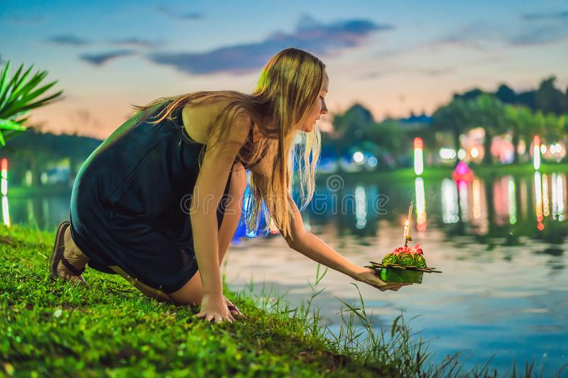 A female tourist holds the Loy Krathong in her hands and is about to launch it into the water. Loy Krathong festival. People buy flowers and candle to light royalty free stock image