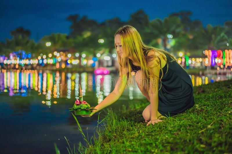 A female tourist holds the Loy Krathong in her hands and is about to launch it into the water. Loy Krathong festival. People buy flowers and candle to light stock photo