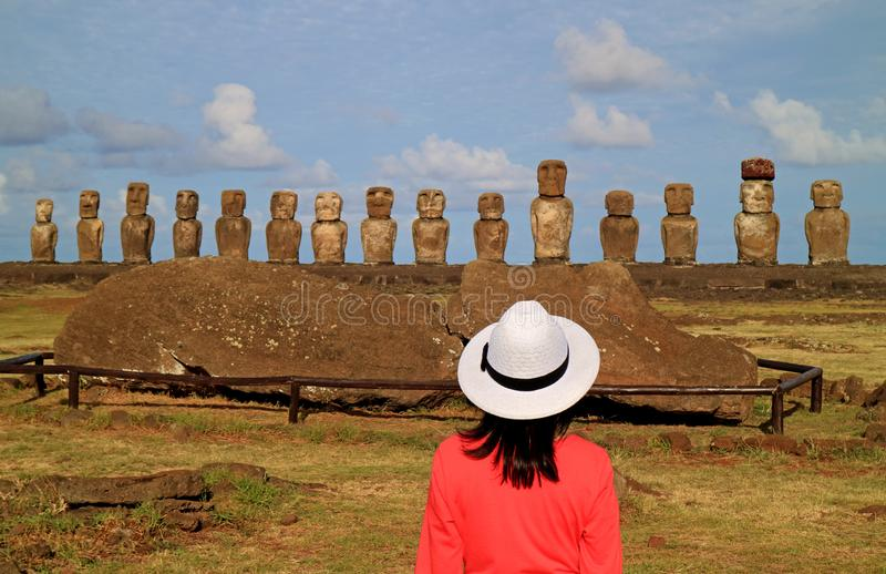 Female tourist impressed by the ruins of Moai statues at Ahu Tongariki on Easter Island archaeological site, Chile royalty free stock images