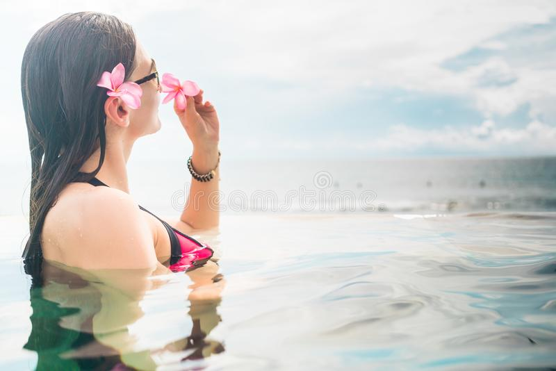 Female Tourist in infinity pool of hotel resort. Showing pink blossom of frangipani flower stock photos