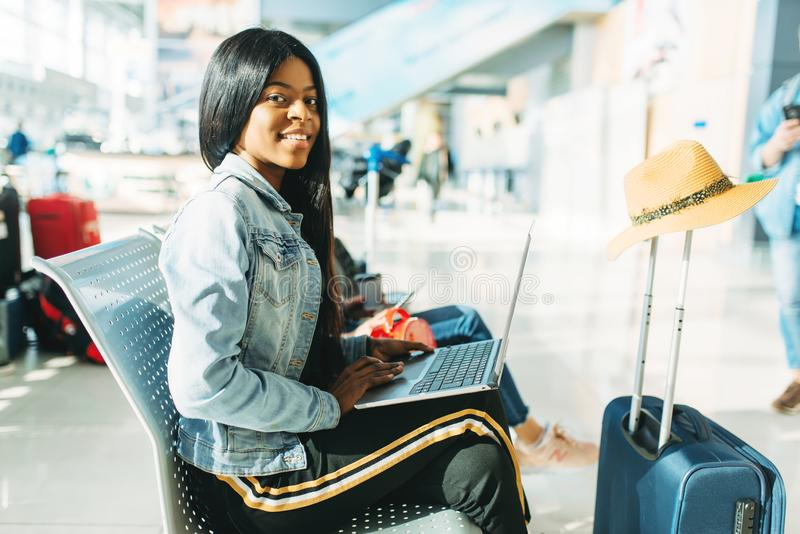 Female tourist with laptop waiting in airport. Female tourist with laptop waiting for departure in airport. Passenger with baggage in air terminal, happy journey royalty free stock image