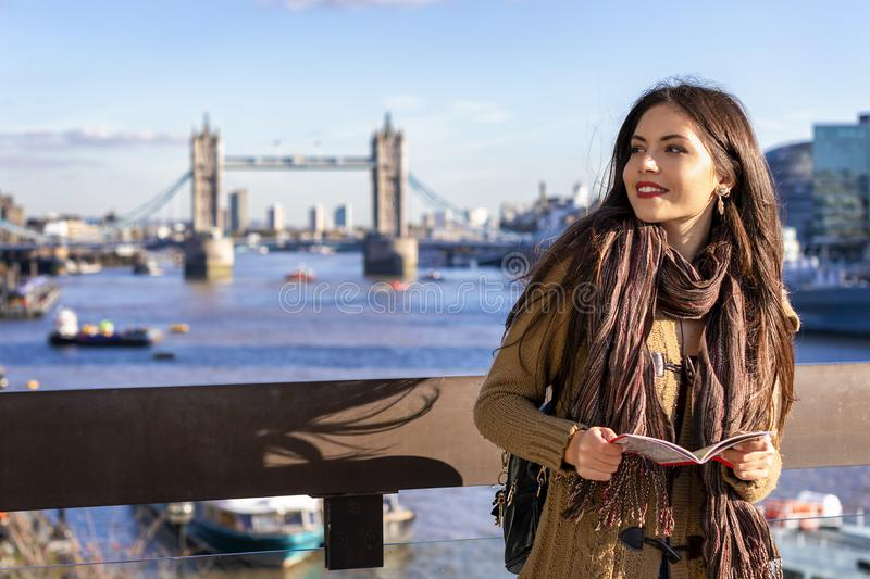 Female tourist in London holding a city map. Beautiful female tourist in London holding a city map in front of the Tower Bridge on a sunny day, UK stock photos
