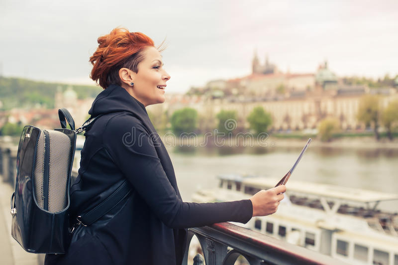 Female tourist looking at city guide. Female tourist standing near river and looking at city guide stock photos