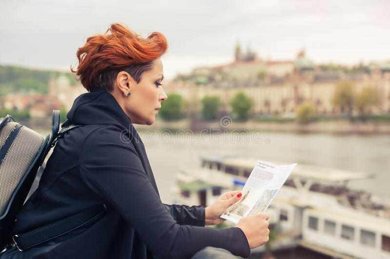 Female tourist looking at city guide. Female tourist standing near river and looking at city guide stock photo