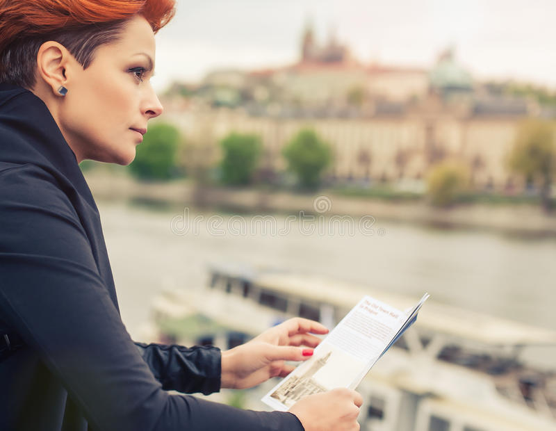 Female tourist looking at city guide. Female tourist standing near river and looking at city guide royalty free stock image