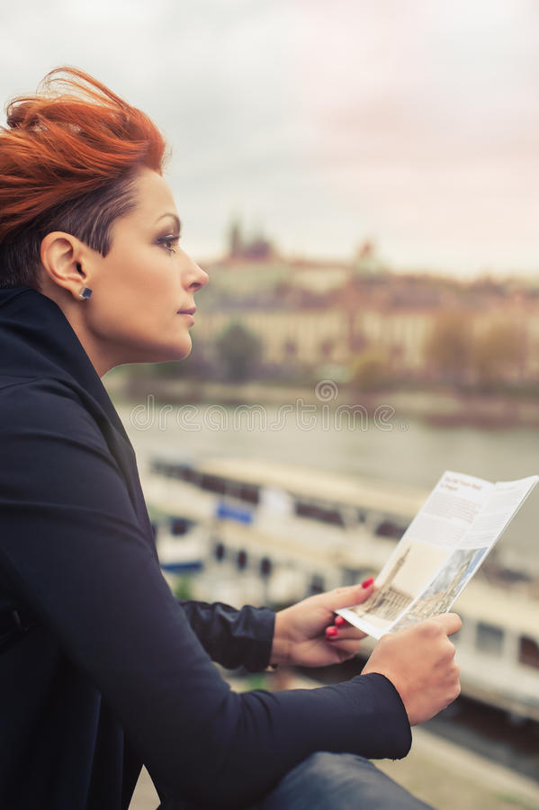 Female tourist looking at city guide. Female tourist standing near river and looking at city guide stock images