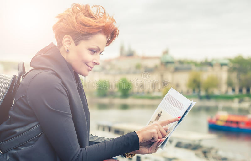 Female tourist looking at city guide. Female tourist standing near river and looking at city guide royalty free stock images