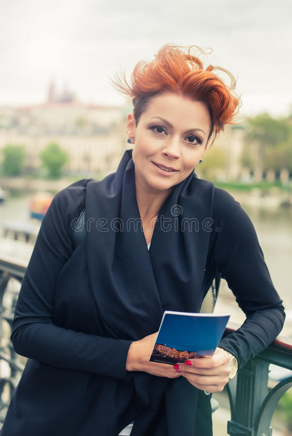 Female tourist looking at city guide. Female tourist standing near river and looking at city guide royalty free stock photos