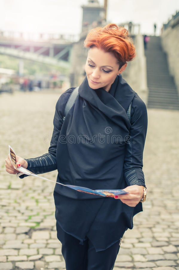 Female tourist looking at city guide. Female tourist standing near river and looking at city guide royalty free stock photography