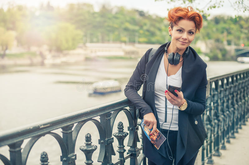 Female tourist looking at mobile phone. Young female tourist with headphones looking at mobile phone and holding city guide royalty free stock image