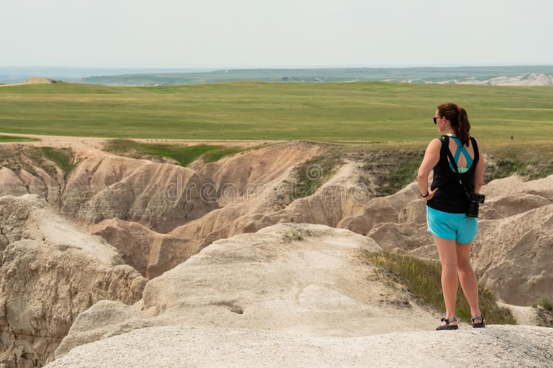Female Tourist Looks Out Over Badlands. Rock Formations royalty free stock photography