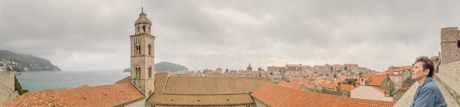 Female Tourist Looks Over Dubrovnik from the City Walls royalty free stock photography