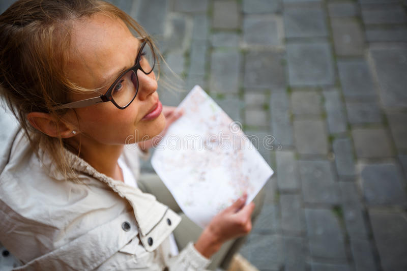 Female tourist with a map discovering a foreign city. & x28;shallow DOF; color toned image& x29 stock photo