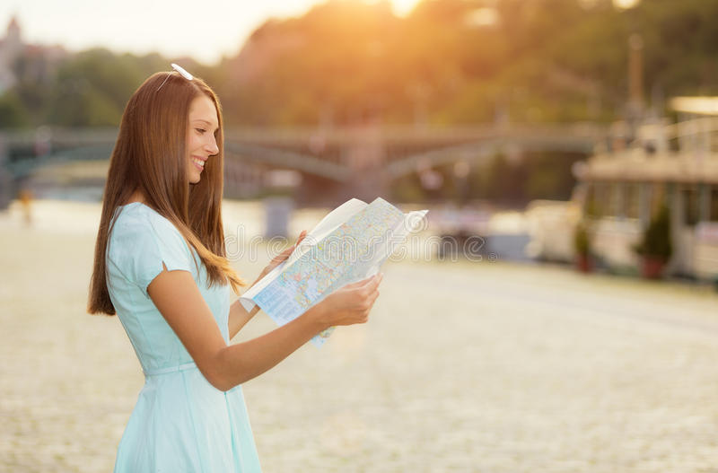 Female tourist with map visiting city. Portrait photography, old town center on background stock photo