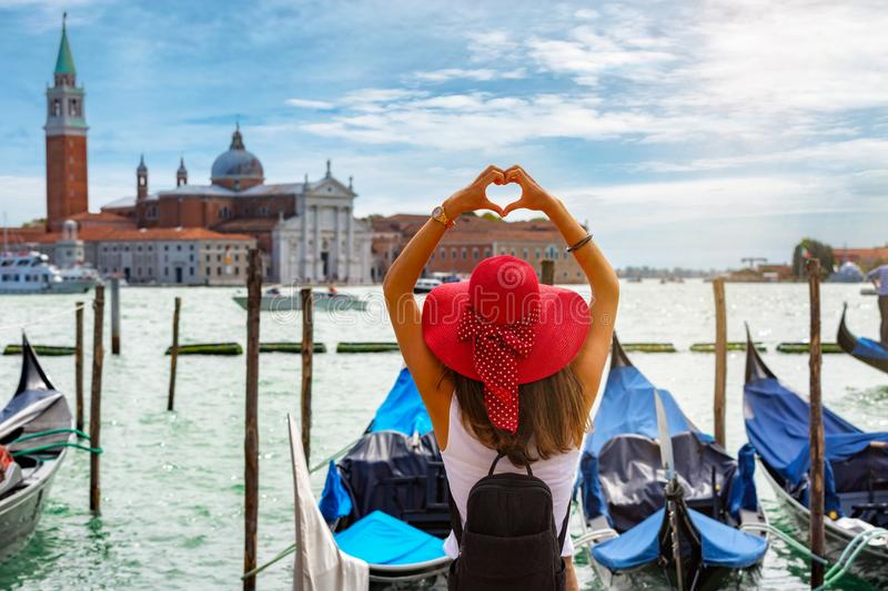 Female tourist on St. Mark`s Square in Venice, Italy. Happy, female tourist shapes a heart with her hands on St. Mark`s Square in Venice, Italy stock photo