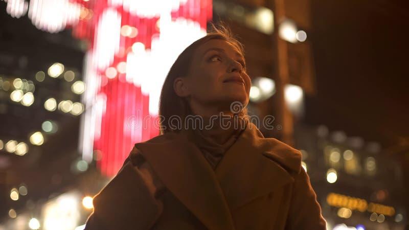Female tourist standing on brightly illuminated street, enjoying festive lights royalty free stock photography