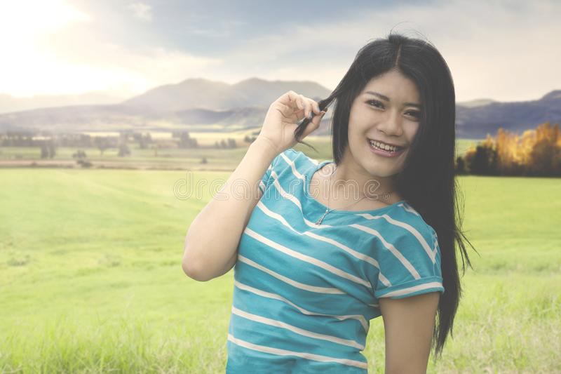 Female tourist standing in the green hill. Picture of female tourist smiling at the camera while standing in the green hill with mountain background stock photo