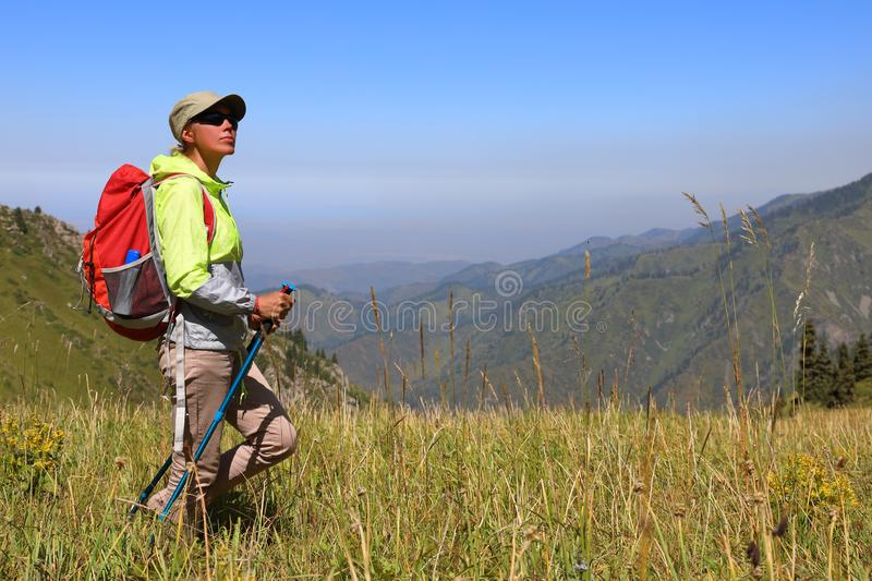 Female tourist stands in the middle of a meadow royalty free stock photography