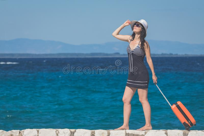Female tourist with suitcase walking by the sea. Travel and summ stock image