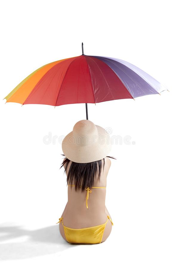 Female tourist with swimsuit and umbrella. Back view of female tourist is wearing swimsuit while holding an umbrella, isolated on white background royalty free stock photo