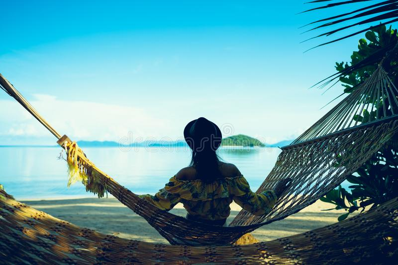 Female tourist swinging in hummock on tropical beach royalty free stock photos