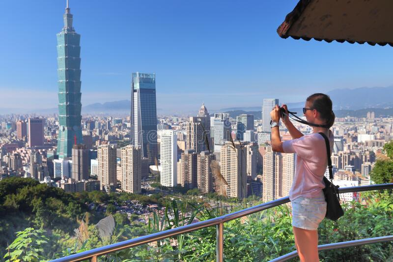 Female tourist in Taipei. Takes photos of city skyline from a viewpoint at Elephant Mountain stock photo