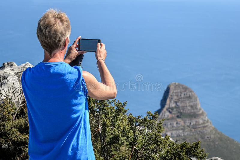 Phone cameras for holiday snapshots by female tourist. Female tourist taking photogrphs with phone camera of Lions Head mountain in Cape Town South Africa from stock photography