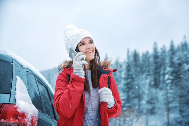 Female tourist talking on cellphone. In snowy countryside royalty free stock photo