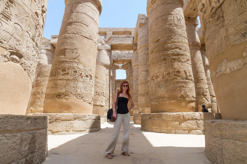 Female Tourist at Temples of Karnak, ancient Thebes in Luxor, Egypt. Female Tourist at Great Hypostyle Hall at the Temples of Karnak, ancient Thebes in Luxor stock photography
