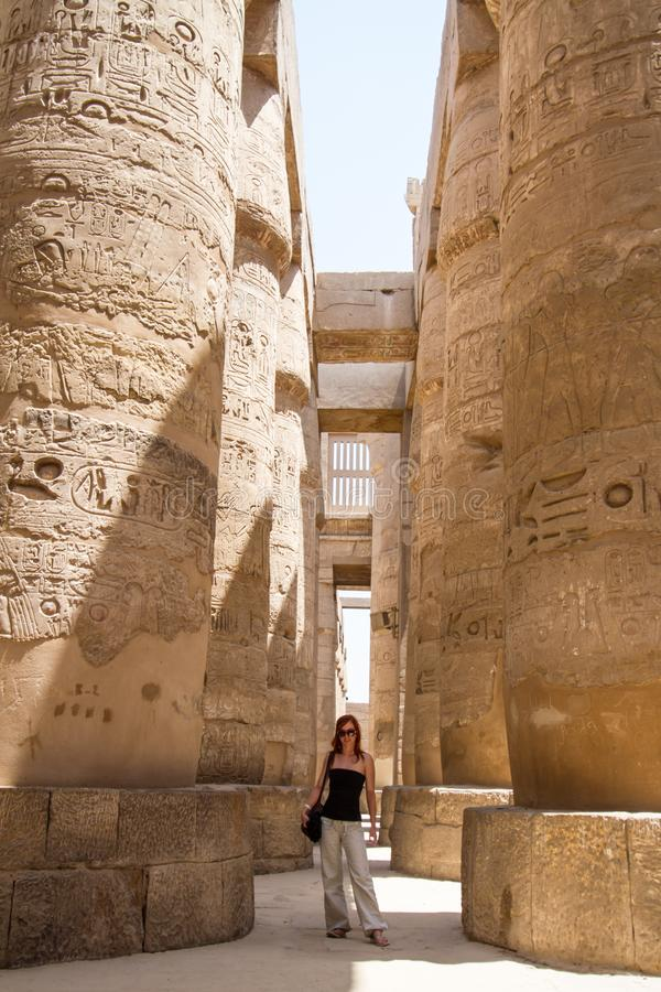 Female Tourist at Temples of Karnak, ancient Thebes in Luxor, Egypt. Female Tourist at Great Hypostyle Hall at the Temples of Karnak, ancient Thebes in Luxor royalty free stock image