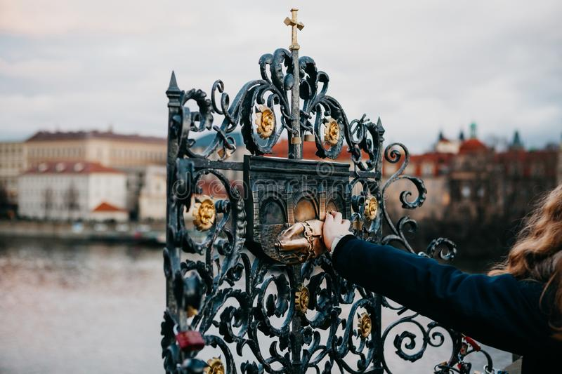 A female tourist touches a bronze statue of John of Nepomuk on Charles Bridge in Prague. For good luck so that dreams come true. An old urban legend says that stock image