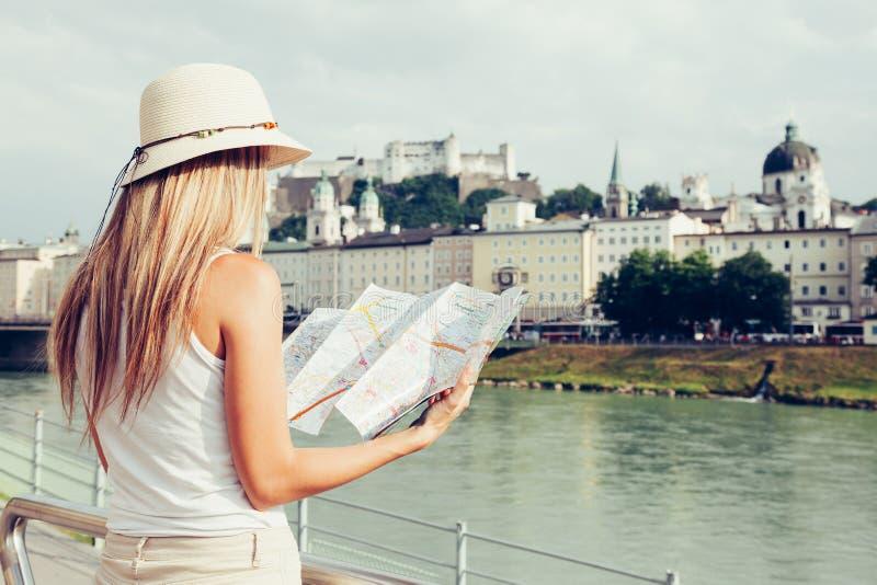 Female tourist on vacation in Salzburg Austria holding a local map. A female tourist on vacation in Salzburg Austria holding a local map stock photo