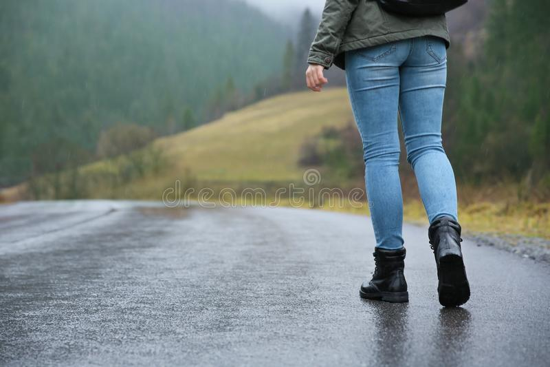 Female tourist walking along countryside road. In the rain royalty free stock photos