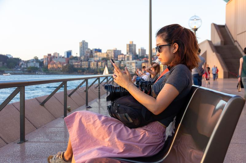 Female tourist wering sunglasses and sit on a bench and watchingmobile phone during sunset at waterfront stock image